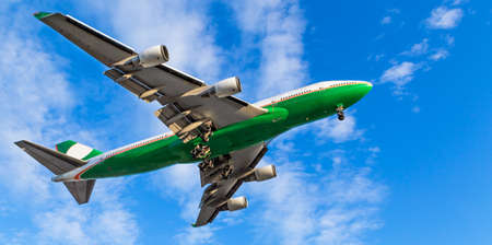 A green and white 747 landing at Vancouver International Airport on a sunny day. Stock Photo