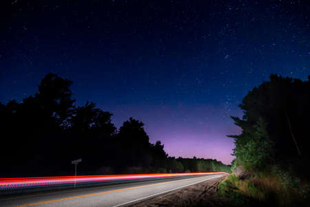Light trail of a passing car on a rural road at night.