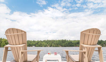 Muskoka chairs overlooking the lake with a bowl of cherries and a glass of champagne in between.
