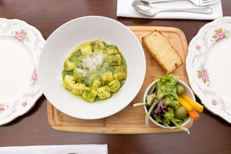 Plate of gnocchi with pesto and a side salad.