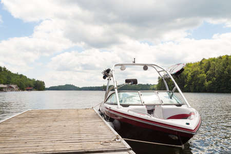 A wakeboard boat at a wooden dock in the Muskokas on a sunny day