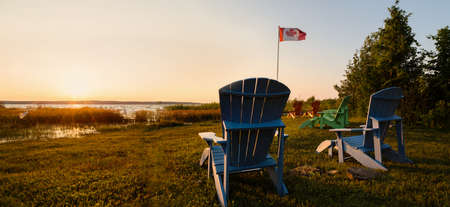 Muskoka chairs on a lawn beside a lake with a Canadian flag in the background at sunset.