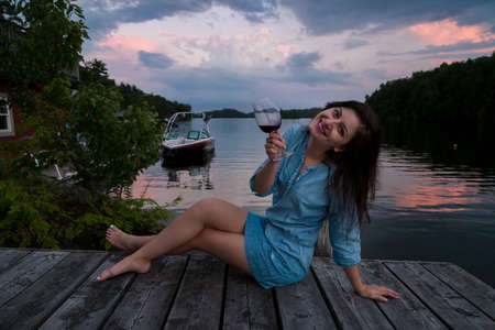 Young brunette woman sitting on a lakeside dock at sunset enjoying a glass of red wine. 免版税图像