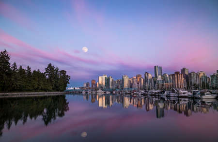 Moon over Downtown Vancouver at sunset from Stanley Park. Stock Photo