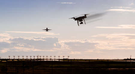 A silhouette of a drone rapidly moving towards an departing aircraft near a airport. Stock fotó