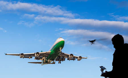 A sihouette of a man flying a drone near a approaching aircraft. Foto de archivo - 128327281