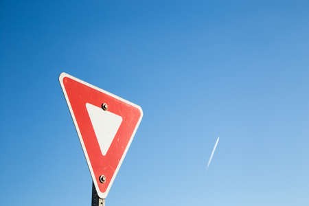 Yield sign against a blue sky with a contrail.