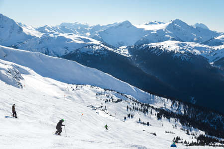 Skiers on a hill at the top of Blackcomb, 7th Heaven, with a view looking toward Whistler on a sunny day. Stock Photo