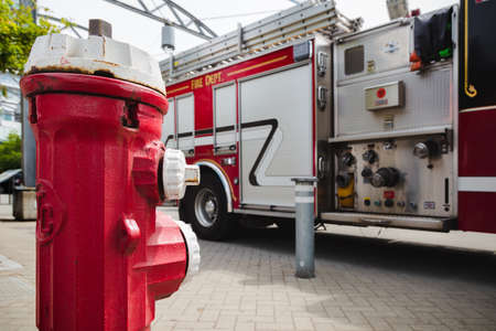 A red fire hydrant in front of a large red fire truck with plumbing for water hose attachments visible. Banque d'images - 129519859