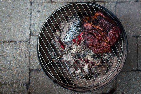 A top down view of a large beef brisket and being barbequed on a small charcoal hibachi grill with glowing coals underneath.