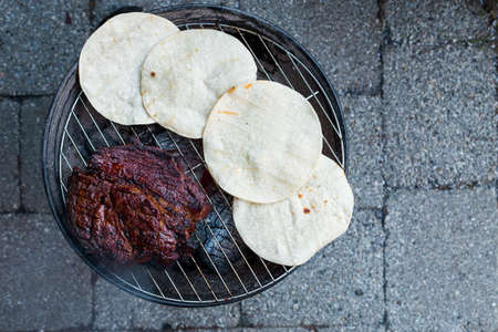 A large beef brisket and and corn tortillas being barbequed on a small charcoal hibachi grill with glowing coals underneath.