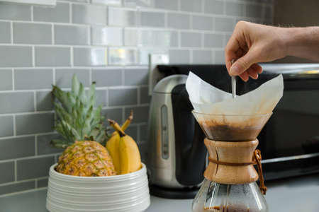 Close-up of a mans hand stirring coffee in a drip coffee flask with a fruit bowl in the background.