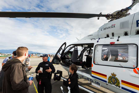 ABBOTSFORD, BC, CANADA - AUG 11, 2019:: A RCMP talking to the public beside a police helicopter at the Abbotsford International Airshow.