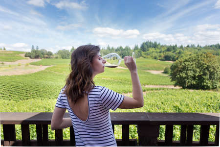 Attractive young brunette woman at a beautiful winery with a glass of red wine. 写真素材