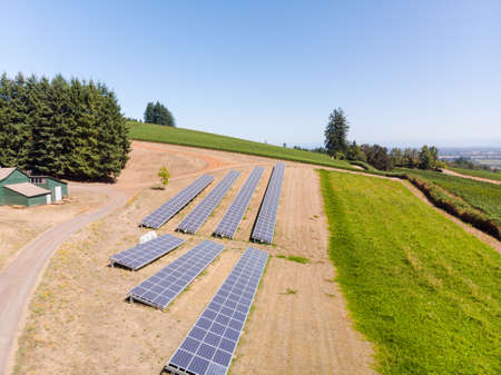 Aerial view of a solar panel array in rural Oregon overlooking a valley.