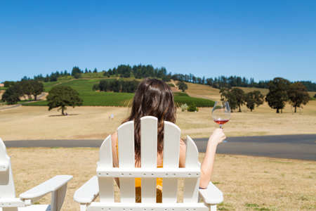 Attractive young brunette woman at a beautiful winery with a glass of red wine.