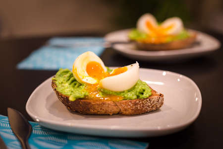 Two plates with a healthy breakfast of avocado on toast with a soft boiled egg.