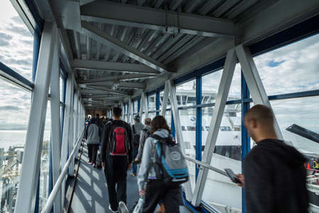 A passenger ferry terminal gangway with travellers walking with their luggage towards a ferry waiting to depart