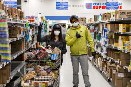 NORTH VANCOUVER, BC, CANADA - MAR 19, 2020: Shoppers at a local supermarket stocking up on groceries in anticipation of supply shortages over the coming weeks as the Coronavirus pandemic worstens.