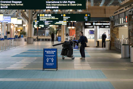 RICHMOND, BC, CANADA - MAR 29, 2020: Traveller in the international departures section of YVR which is nearly empty due to the COVID-19 coronavirus pandemic.
