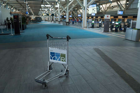 RICHMOND, BC, CANADA - MAR 29, 2020: Luggage cart in the international departures area of YVR that is completely empty due to the COVID-19 coronavirus pandemic. 新聞圖片