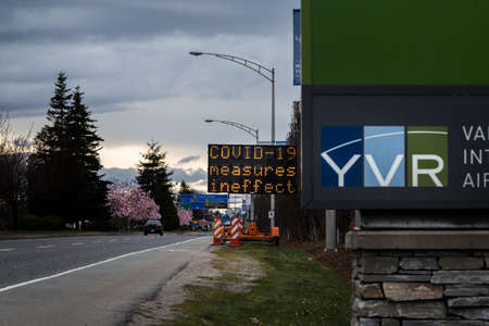 RICHMOND, BC, CANADA - MAR 29, 2020: An electronic road sign at YVR airport displaying public health notices related to the COVID-19 coronavirus pandemic. 新聞圖片