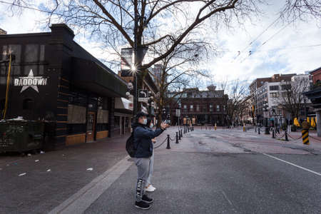 DOWNTOWN VANCOUVER, BC, CANADA - APR 01, 2020: Local street photographer capturing the scene in Gastown of desolation due to the Covid 19 pandemic 新聞圖片
