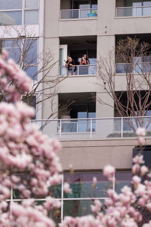 DOWNTOWN VANCOUVER, BC, CANADA - APR 01, 2020: Roomates that are self quarantining coming out on their balcony at 7pm to cheer for Canadian health care workers. 新聞圖片