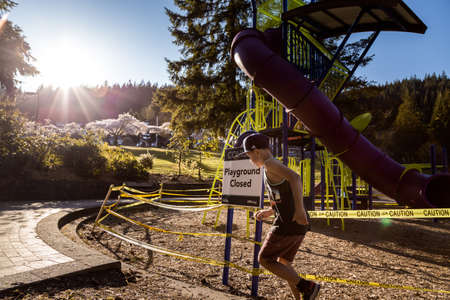 NORTH VANCOUVER, BC, CANADA - APR 11, 2020: Children play outside a closed off playground in a North Vancouver public park lined with caution tape to aid in curbing the spread of the Covid 19 virus. 版權商用圖片 - 144820106