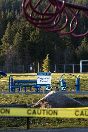 NORTH VANCOUVER, BC, CANADA - APR 07, 2020: A closed off playground in a North Vancouver public park lined with caution tape to aid in curbing the spread of the Covid 19 virus 新聞圖片