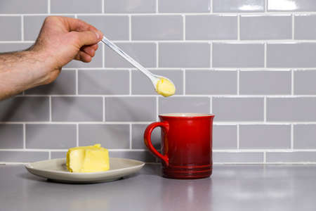 Mans hand holding a teaspoon of butter with a red coffee mug to make bulletproof coffee. Stock Photo