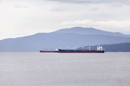 Cargo and tanker ships moored in Vancouver harbor awaiting to be loaded.