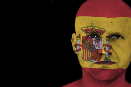 man with spanish flag painted on his face photo