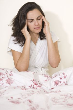 Young woman with headache sitting on her bed photo