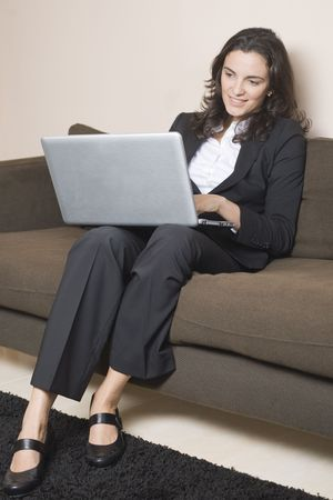 good-looking woman sitting on couch and surfing in internet photo