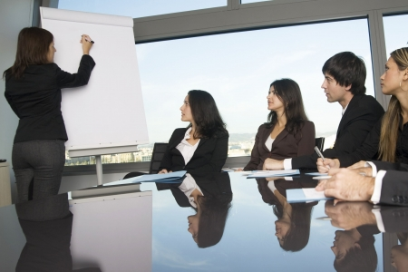 Business training where group of persons is sitting at a table with the teacher standing in front of a flip chart photo