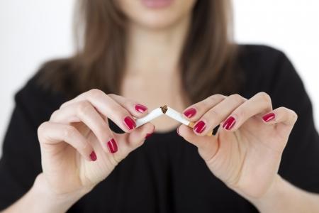 no fumar: mujer joven rompe un cigarrillo Foto de archivo