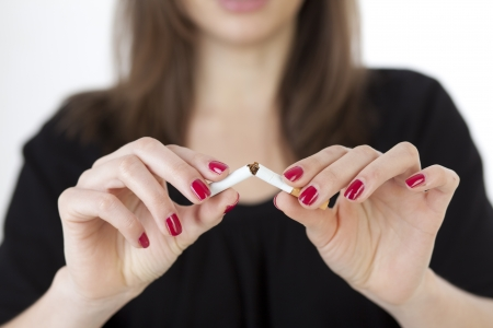 unhealthy living: young woman breaks a cigarette Stock Photo