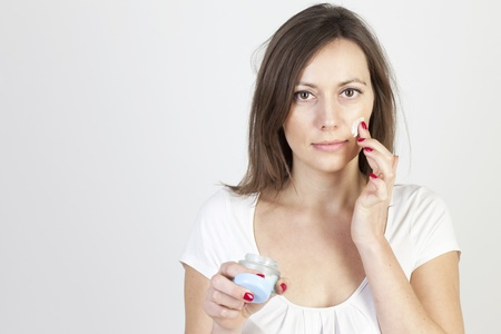 Woman applying lotion on her face photo