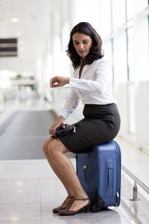 delay:  Good-looking latin businesswoman waiting at the airport