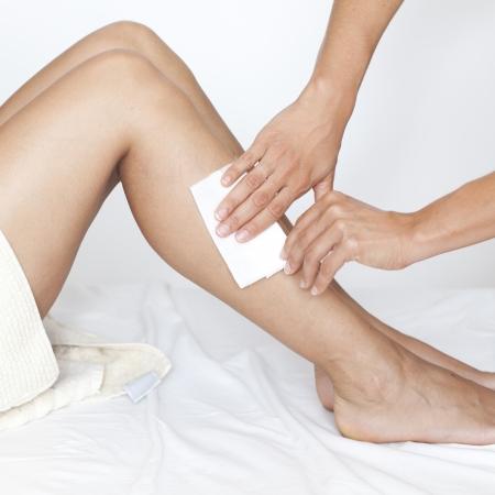depilacion con cera: La eliminación del vello de las piernas de la mujer Foto de archivo