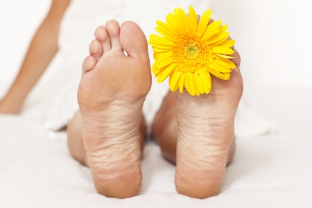 body scape: Woman foot with yellow flower between fingers