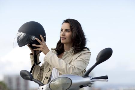 motorrad frau: Attraktive Frau startet ihren Helm