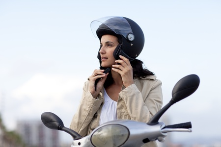 moped: Attractive woman takes off her helmet Stock Photo