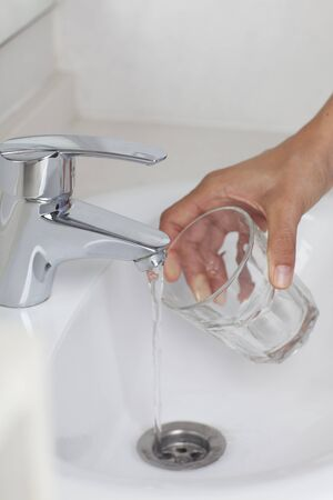 Hand filling glas with water  photo