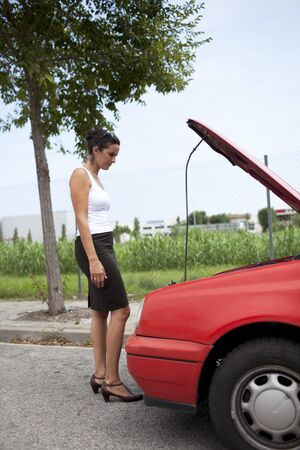 Woman watching the engine of a broken car photo