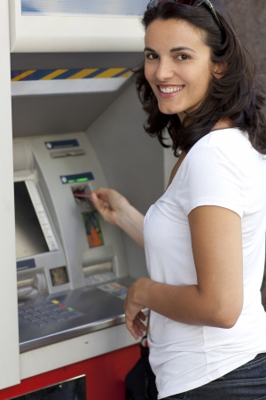 debit card: Woman inserts card in the ATM Stock Photo