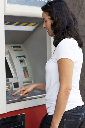 Good-looking latin woman enters the PIN number at the ATM