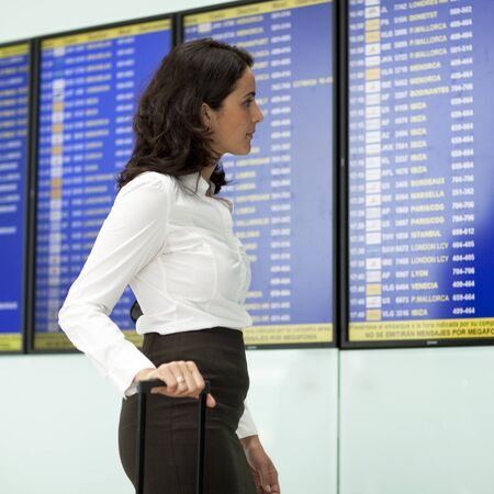 stewardess: Woman checking destination board at the airport