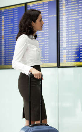 Woman checking destination board at the airport photo